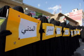 Iraqi women hold up placards in support of the 'Jaafari Personal Status Law' in the shrine city of Najaf in central Iraq on March 12 2014 The law...