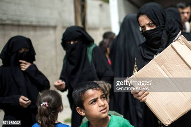 Iraqi women in west Mosul receive aid packages given by volunteers from the eastern side on April 21 as Iraqi forces continue the offensive to retake...