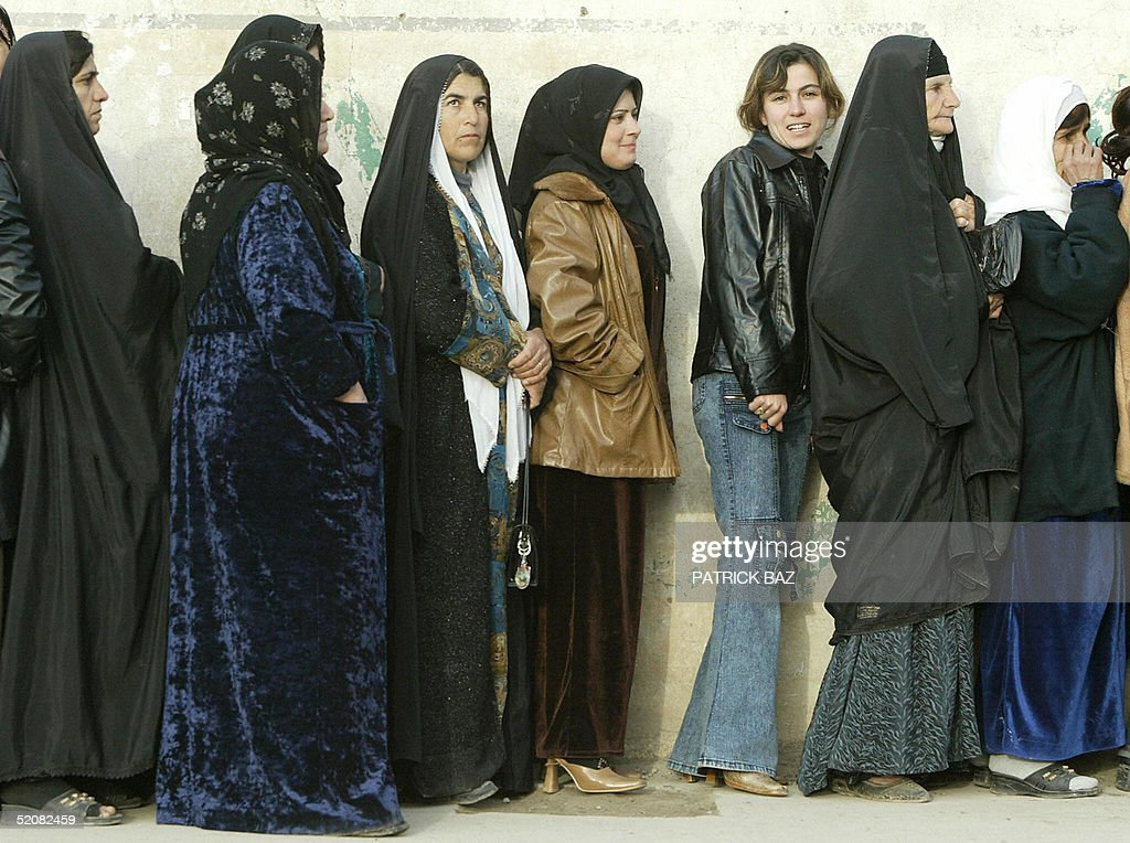 Iraqi women line up outside a polling station waiting to vote in the Iraqi northern Kurdish city of Suleimaniya 30 January 2005 Iraqi Kurds flocked...