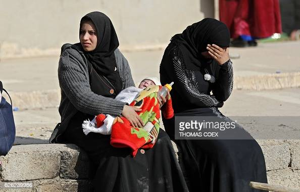 Iraqi women sit walk as they flee their neighbourhoods to safer locations on November 28 2016 in an eastern district of the city of Mosul during the...