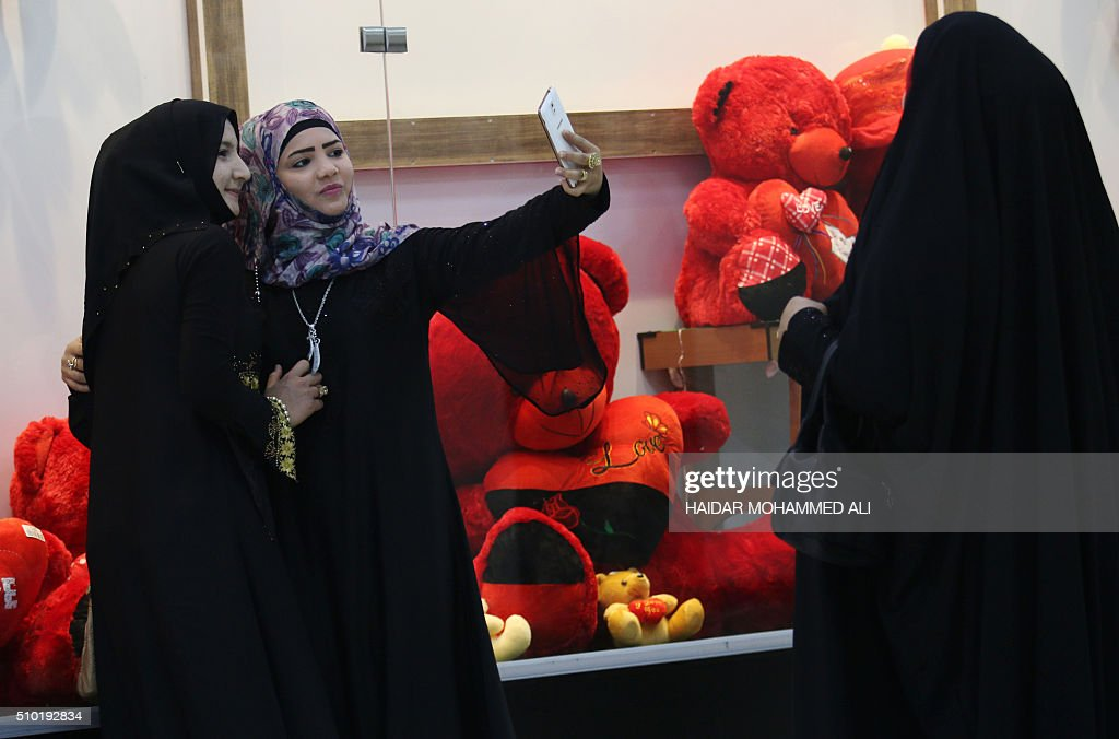 Iraqi women take a selfie in front of a shop selling Valentine's day gifts on February 14, 2016, in the mainly Shiite southern city of Basra. / AFP / HAIDAR MOHAMMED ALI
