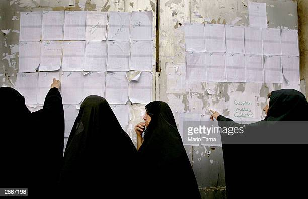 Iraqi women view lists of names of those selected to attend the Hajj pilgrimage next month in Mecca Saudi Arabia January 14 2004 in Baghdad Iraq...