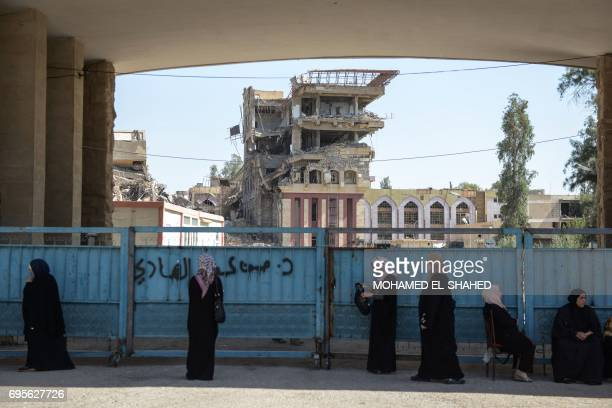 Iraqi women wait outside the University of Mosul as students arrive to take their exams on June 13 2017 Amid buildings destroyed by heavy fighting...
