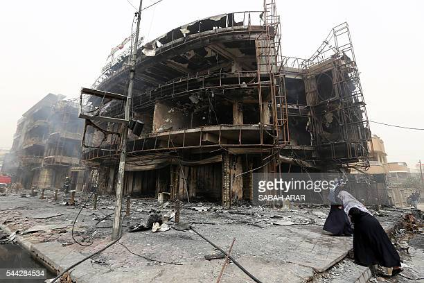 TOPSHOT Iraqi women walk past a damaged building at the site of a suicide car bombing claimed by the Islamic State group on July 3 2016 in Baghdad's...
