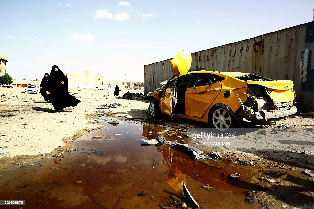 Iraqi women walk past a damaged car following a twin suicide bombing attack, claimed by the Islamic State (IS) group, in the southern Iraqi city of Samawah, situated deep in Iraq's Shiite heartland, on May 1, 2016. HAMDANI