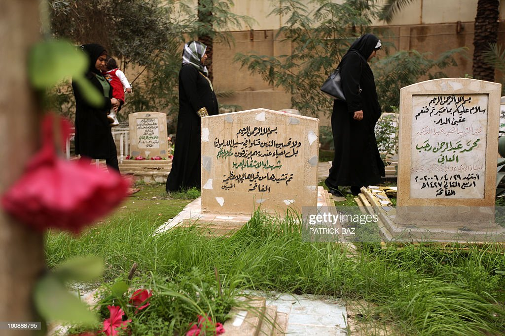 Iraqi women walk past the tomb (C) of two unidentified Arab fighters buried in the Martyrs Cemetery of Baghdad's Adhamiyah Sunni stronghold on February 7, 2013. Hundreds of unidentified Arab fighters mostly from Syria and Egypt who volunteered to fight with Saddam Hussein's forces were killed by US troops during the battle of Baghdad on April 13, 2003.