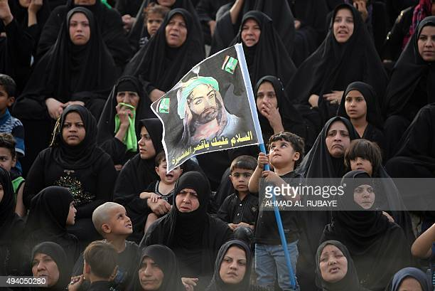 Iraqi women watch the reenactment of the Battle of Karbala on the tenth day of the mourning period of Muharram which marks the day of Ashura on...