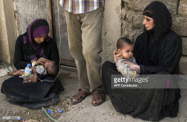 Iraqi women who fled the fighting between government forces and Islamic State group jihadists in the Old City of Mosul hold children while sitting in...