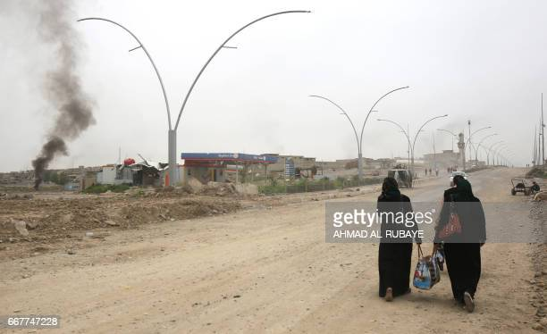 Iraqi women who fled west of Mosul because of the fighting against Islamic State group jihadists walk towards a camp as Iraqi forces advance to...