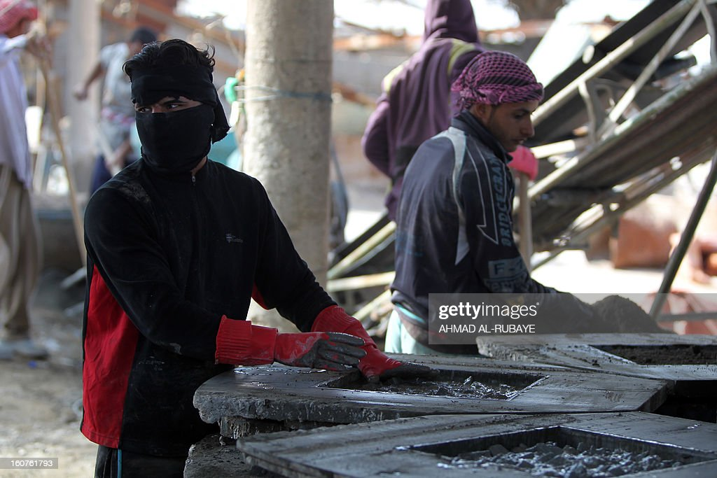 Iraqi workers prepare molds for tiles used in flooring at a factory in the town of Taji, just north of the capital Baghdad, on February 5, 2013. Unemployment is high across Iraq with these 16 employees at this factory earning some twenty thousand Iraqi dinars a day (about $15) for working an 11 hour day.