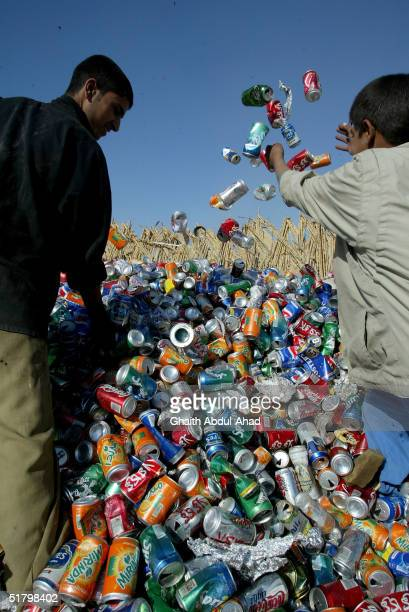 Iraqi workers rearrange metal cans in a recycling depot on November 21 2004 in Baghdad Iraq A thriving recycling industry has begun to flourish in...