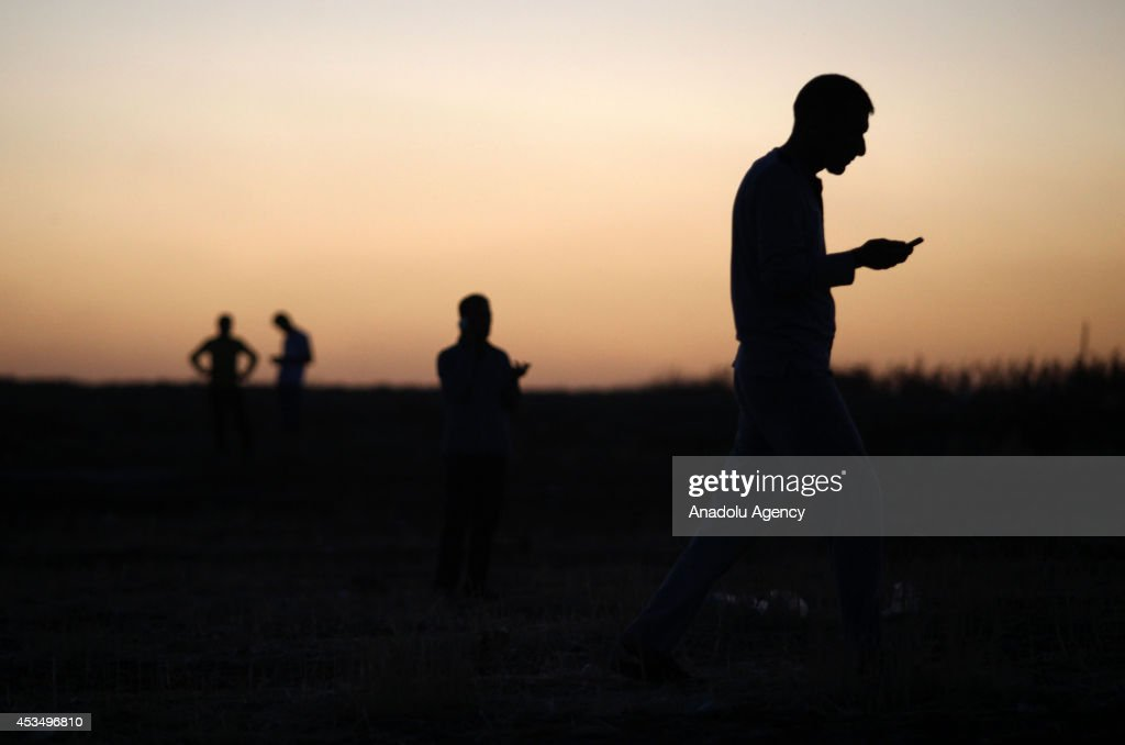 Iraqi Yezidi people try to get an efficient cell signal near cell towers in Sirnak, Turkey on August 11, 2014 in order to make phone calls to talk with their relatives back home in Iraq. Iraqi Yezidi people flee Sinjar town of Mosul to Silopi district of Turkey's Sirnak city due to the attacks of Islamic State-led armed groups.Refugees crossed the Habur border, fleeing attacks from Islamic State fighters, formerly known as ISIL to houses 3 kilometers away from Silopi district, Turkey.