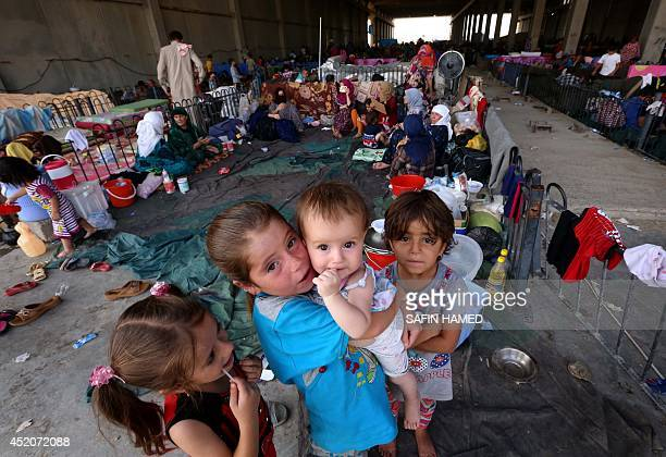 Iraqi young children who fled violence in the northern city of Tal Afar with their families pose at the Bahrka camp that hosts displaced people 10 km...