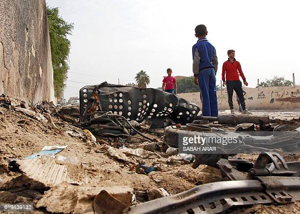 Iraqi youth gather by wreckage at the site of a car bomb that exploded the previous night in Baghdad's Hurriyah neighbourhood on October 31 2016 The...