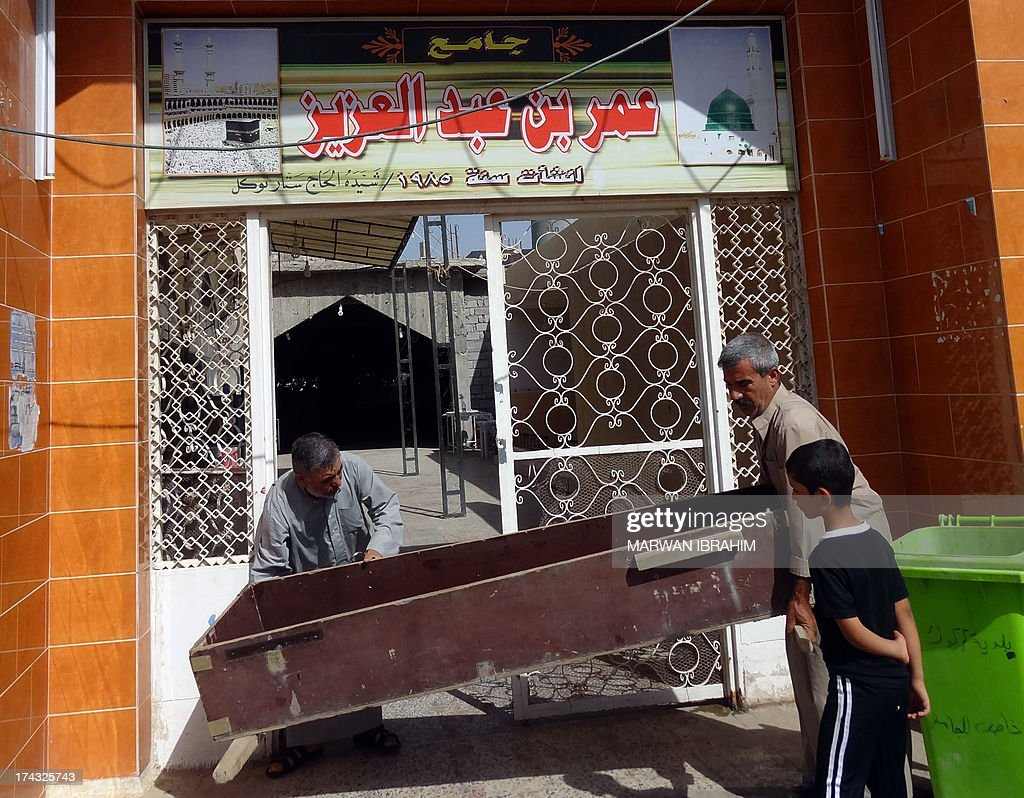 Iraqis carry a coffin into the Omar bin Abdulaziz Mosqe in the northern city of Kirkuk on July 24, 2013 a day after it was hit by a bomb explosion. Bombs targeting worshippers gathered for evening prayers at four Sunni mosques in Iraq killed 12 people, officials said.