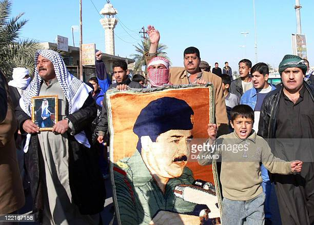 Iraqis carry portraits of executed former dicator Saddam Hussein during a demonstration against his hanging in Saddam's hometown of Tikrit 30...