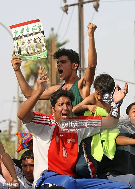 Iraqis celebrate after Iraq's National soccer team won against South Korea during the 2007 AFC Asian Cup semifinal soccer match in the Karrada...