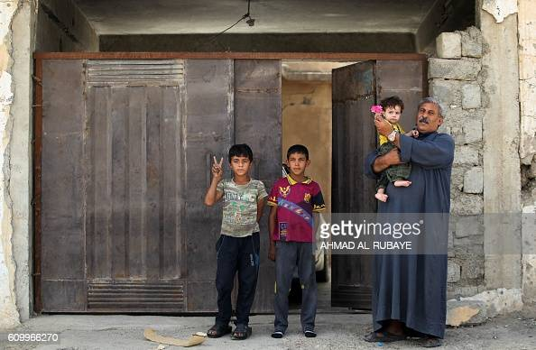 Iraqis celebrate outside their house in the town of Sharqat around 80 kilometres south of the city of Mosul on September 23 the day after Iraqi...