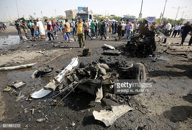Iraqis check the damage after a suicide bomber detonated an explosivesrigged vehicle in northern Baghdad's Sadr City on May 17 2016 security and...