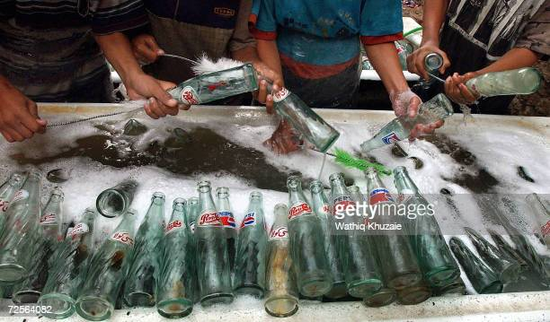 Iraqis clean bottles before filling them with fake Pepsi in a factory November 5 2004 in Baghdad Iraq Most of the goods sold on the Iraqi market are...