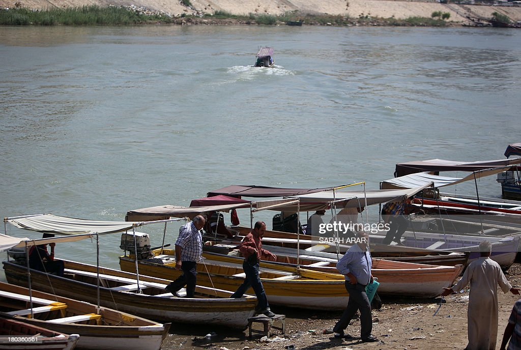 Iraqis debark from boats after crossing the Tigris River which flows through the Iraqi capital of Baghdad on September 11 2013 Faced with a surge in...