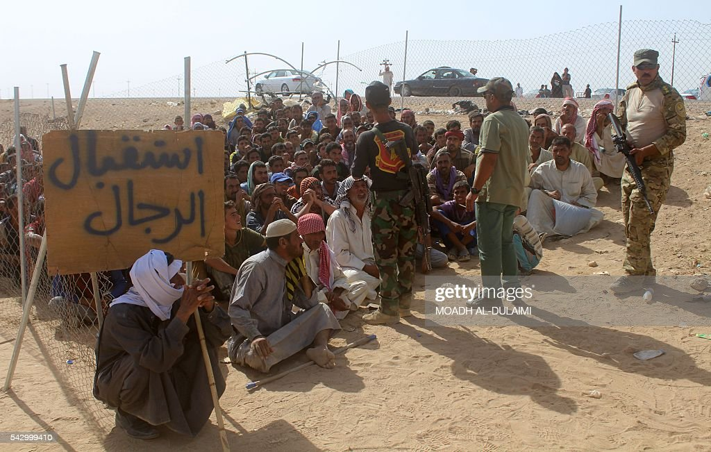 Iraqis displaced from al-Buthiab area north of Ramadi sit and wait to be inspected by government forces as they arrive at a makeshift camp, 18 kms west of the capital of Anbar province, where they are taking shelter, on June 25, 2016. Iraqi government forces retook control of the city of Ramadi from the Islamic State (IS) group in February 2016 but sporadic IS attacks there have continued. / AFP / MOADH