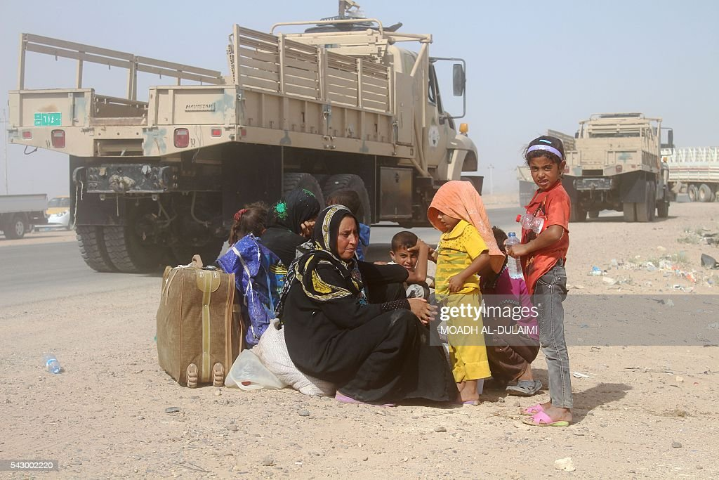 Iraqis displaced from al-Buthiab area north of Ramadi sit on the side of a street after arriving at a makeshift camp, 18 kms west of the capital of Anbar province, where they are taking shelter, on June 25, 2016. Iraqi government forces retook control of the city of Ramadi from the Islamic State (IS) group in February 2016 but sporadic IS attacks there have continued. / AFP / MOADH