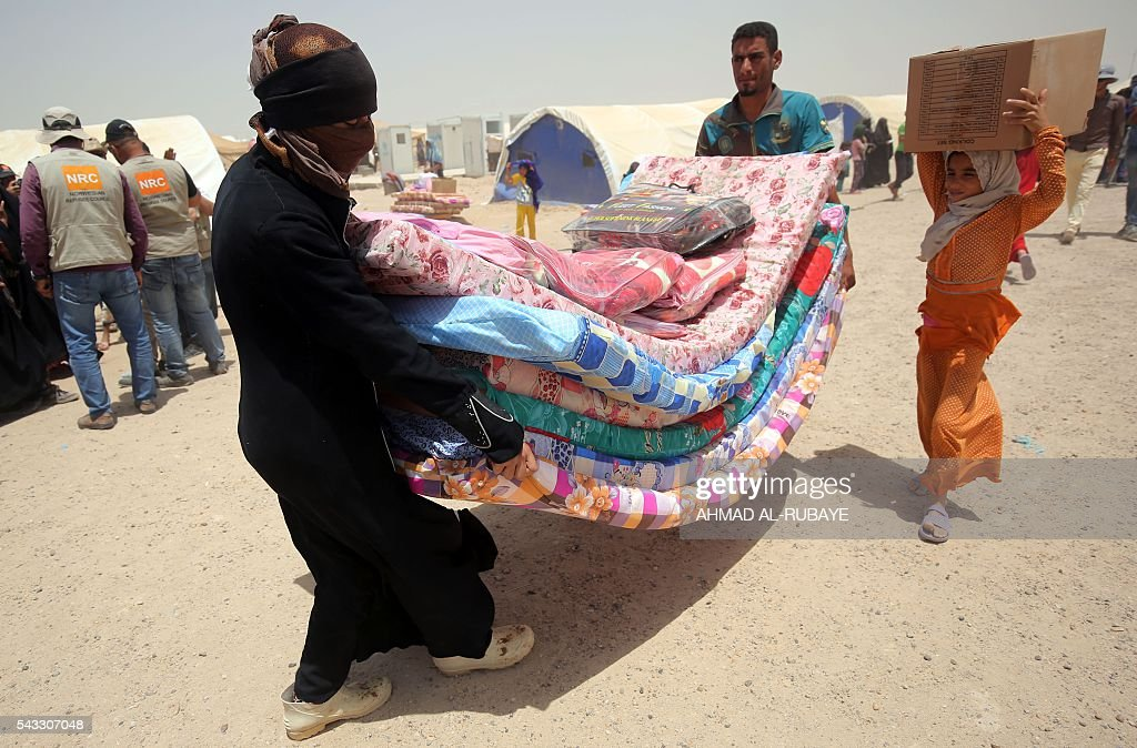 Iraqis displaced from the city of Fallujah collect aid distributed by the Norwegian Refugee Council at a newly opened camp where they are taking shelter in Amriyat al-Fallujah on June 27, 2016, south of Fallujah. Iraqi forces on June 26 wrapped up operations in Fallujah and declared the area free of jihadists from the Islamic State (IS) group after a month-long operation. The government said the destruction caused by the fighting was limited and vowed to do its utmost to allow the tens of thousands of displaced civilians to return to their homes. RUBAYE