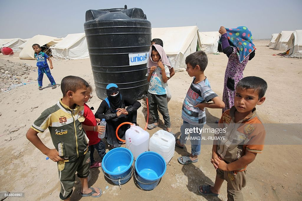Iraqis displaced from the city of Fallujah gather next to a water tank at a newly opened camp where they are taking shelter in Amriyat al-Fallujah on June 27, 2016, south of Fallujah. Iraqi forces on June 26 wrapped up operations in Fallujah and declared the area free of jihadists from the Islamic State (IS) group after a month-long operation. The government said the destruction caused by the fighting was limited and vowed to do its utmost to allow the tens of thousands of displaced civilians to return to their homes. RUBAYE