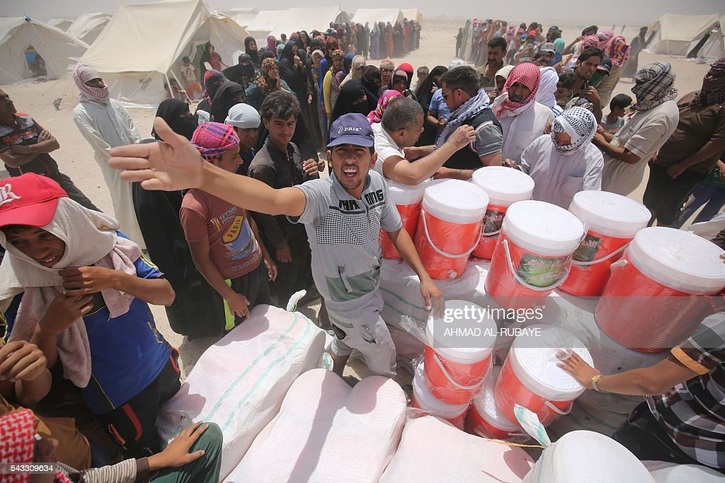 Iraqis displaced from the city of Fallujah queue up to collect aid distributed by the Norwegian Refugee Council at a newly opened camp where they are taking shelter in Amriyat al-Fallujah on June 27, 2016, south of Fallujah. Iraqi forces on June 26 wrapped up operations in Fallujah and declared the area free of jihadists from the Islamic State (IS) group after a month-long operation. The government said the destruction caused by the fighting was limited and vowed to do its utmost to allow the tens of thousands of displaced civilians to return to their homes. RUBAYE