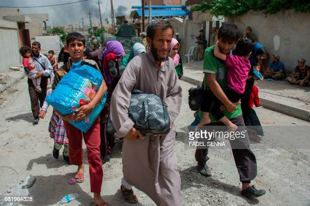 Iraqis evacuate their home as Iraqi forces advance in the northwestern alHaramat neighbourhood of Mosul on May 11 during the ongoing offensive to...