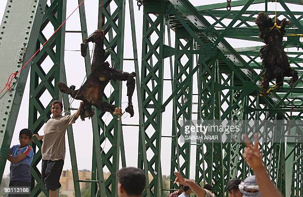 Iraqis flash the �V� for victory sign as charred bodies hang from a bridge over the Euphrates River in the flashpoint town of Fallujah 50 kms west of...