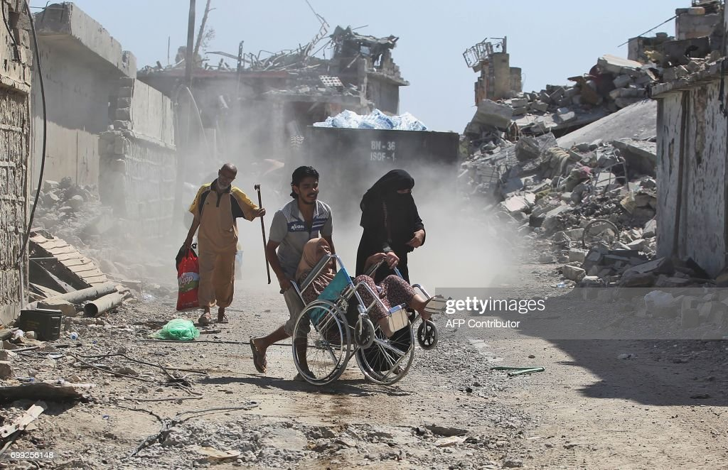 Iraqis flee from the Old City of Mosul on June 21, 2017, during the ongoing offensive by Iraqi forces to retake the last district still held by the Islamic State (IS) group. /