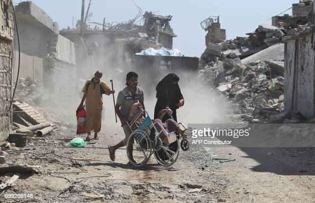Iraqis flee from the Old City of Mosul on June 21 during the ongoing offensive by Iraqi forces to retake the last district still held by the Islamic...