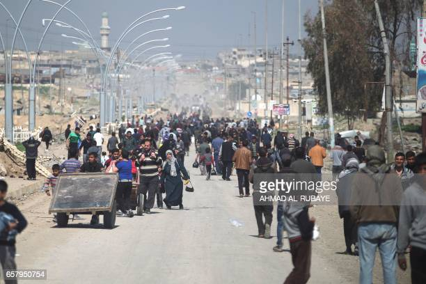 TOPSHOT Iraqis fleeing the fighting against Islamic State group are seen in Mosul on March 26 2017 as an ongoing operation against the jihadists...