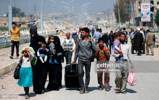 TOPSHOT Iraqis fleeing their homes in Mosul's old city carry their belongings as they leave the fighting area on March 30 due to the ongoing battles...