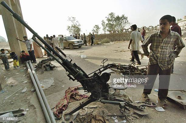 Iraqis gather around weapons including an antiaircraft gun at a stadium in Baghdad's Shiite slum of Sadr City 17 October 2004 Mortars landed near the...