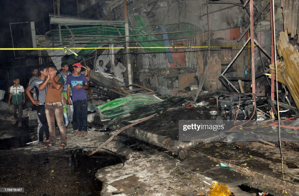 Iraqis gather at the scene of an explosion in Nasiriyah, south of the Iraqi capital Baghdad on August 10, 2013. Car bombs ripped through Baghdad cafes and markets while blasts and shootings struck elsewhere on August 10, killing 61 people as Iraq marked the end of its deadliest Ramadan holy month in years. AFP PHOTO STR