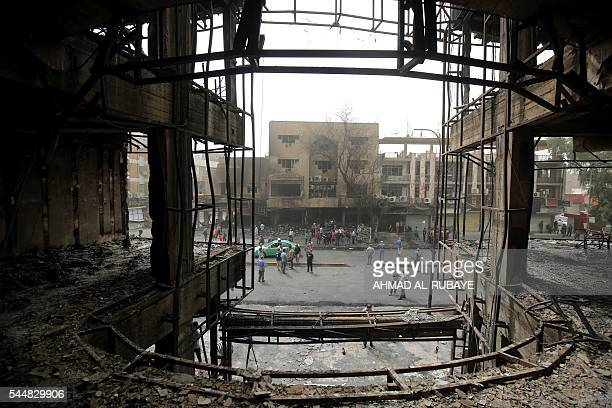Iraqis gather on July 4 2016 around a building damaged by a suicidebombing attack which took place a day earlier in Baghdad's Karrada neighbourhood...