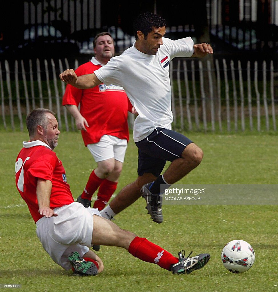 Iraqi's Hassan Turke Atia (up) jumps as he is tackled by Harwich Labour MP Ivan Henderson (down) in London 20 May 2004. UK parliamentary football club plays against the national team of Iraq for a friendly match. Iraq won 11-0. AFP PHOTO Nicolas ASFOURI