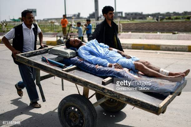 TOPSHOT Iraqis help transport a wounded man lying on a wooden cart in west Mosul on April 21 as Iraqi forces continue the offensive to retake the...
