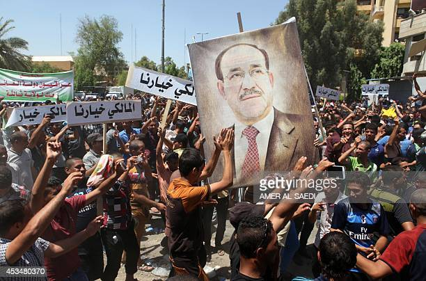 Iraqis hold a giant portrait of Iraq's Prime Minister Nuri alMaliki during a demonstration to support him on August 11 2014 in Baghdad's central...