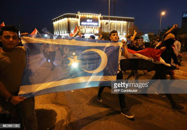 Iraqis hold Iraqi flags and the flag of the Iraqi Turkmen as they gather in the street in the city of Kirkuk to celebrate on October 18 after Iraqi...
