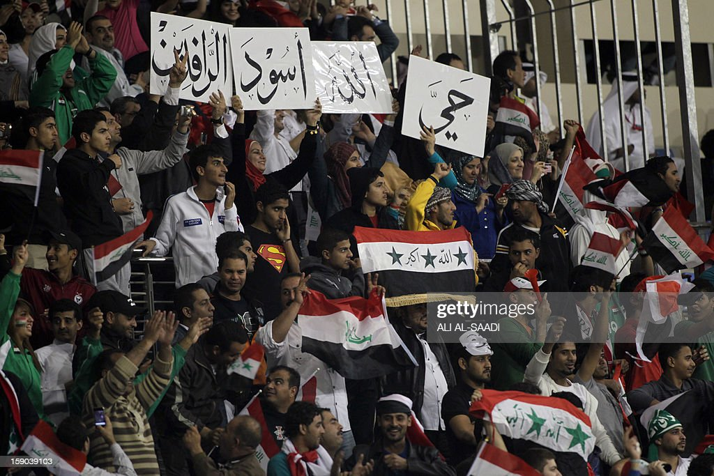 Iraqis hold up placards that read in Arabic, 'God Bless the lions of Mesopotamia' as they cheer their team during their game against Saudi Arabia in the 21st Gulf Cup in Manama, on January 6, 2013. AFP PHOTO/ALI AL -SAADI