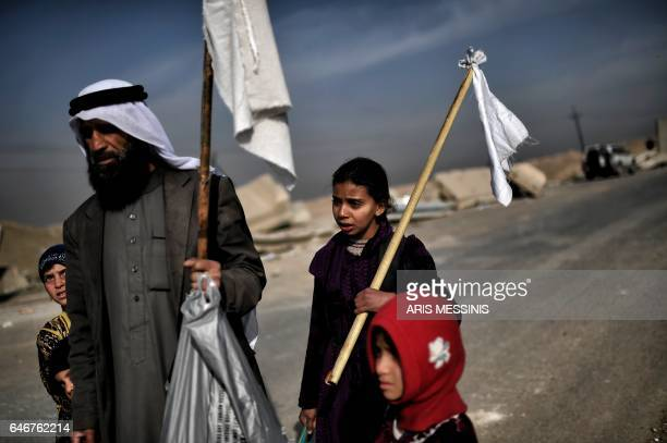 TOPSHOT Iraqis holding white flags walk down a road as they flee Mosul on March 1 during an offensive by security forces to retake the western parts...