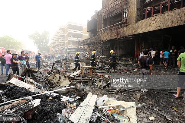 Iraqis including firefighters gather at the site of a suicide car bombing claimed by the Islamic State group on July 3 2016 in Baghdad's central...