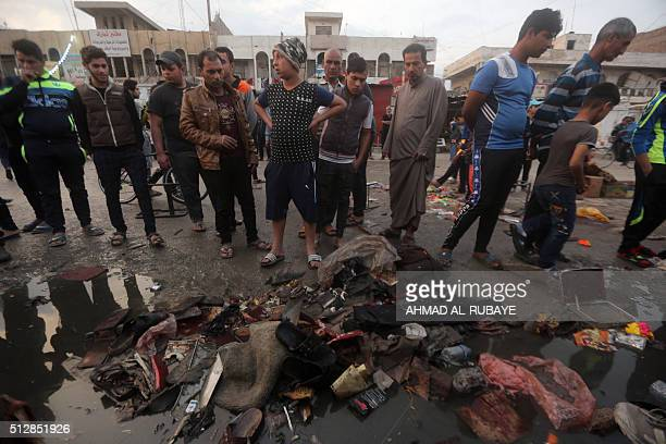 Iraqis inspect the damage at the site of a bombing claimed by the Islamic State group near a market in the Sadr City area of northern Baghdad on...