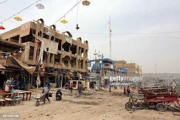 Iraqis inspect the damage on October 6 a day after a car bomb explosion in a busy area in Hosseiniyah barely 20 kilometres north of Baghdad killing...