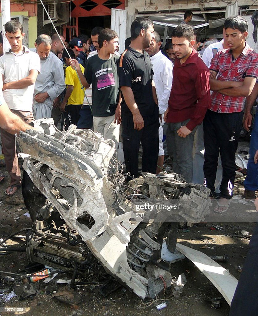 Iraqis inspect the site of a car bomb explosion in Diwaniyah, south of Baghdad, on April 29, 2013. Three car bombs exploded south of Baghdad, killing several people and wounding scores of others, police said, the latest attacks in a seven-day wave of violence that has left more than 230 people dead across Iraq. AFP PHOTO/STR