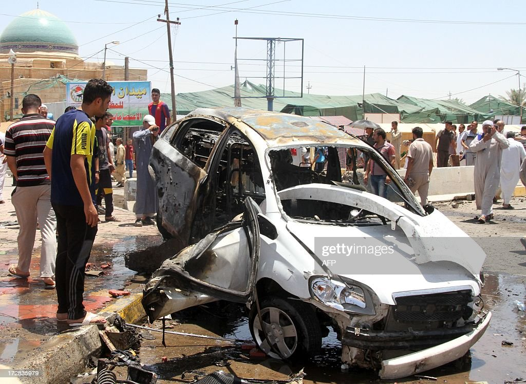 Iraqis inspect the site of a suicide car bomb attack in the Al-Haq square in Samarra, a predominantly Sunni town north of Baghdad, on July 5, 2013. Attacks killed five people in town squares in Iraq, including four who died when a suicide bomber set off his vehicle rigged with explosives just before midday prayers.